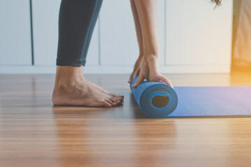 Exercise equipment,Woman hand rolling or folding yoga mat after a workout,Healthy fitness and sport concept