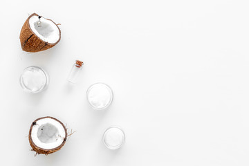 Coconut oil cosmetics for skin and hair care. Oil in small bottle, cream jar, halfs of coconut with shelf on white background top view copy space