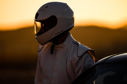 A Helmeted Driver Preparing To Race At Sunrise