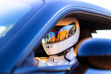 A Helmeted Driver At The Wheel Of His Race Car