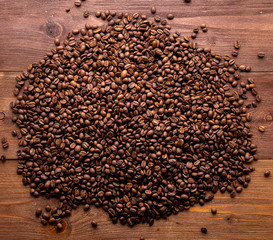 Close-up roasted coffee beans on brown wooden background, top view, copy space