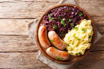 Roasted sausages with steamed cabbage (sauerkraut) and boiled potatoes close-up on a plate. Horizontal top view