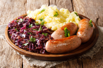 Traditional German Sausages with Mashed Potato and Sauerkraut. Wurst or Bratwurst with red Cabbage close-up on a plate. Horizontal