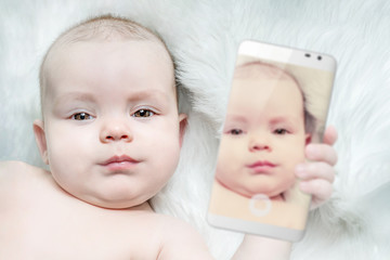 A cute baby is holding a smartphone with his photo