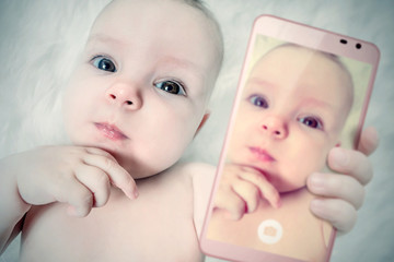 Funny baby girl make selfie on mobile phone