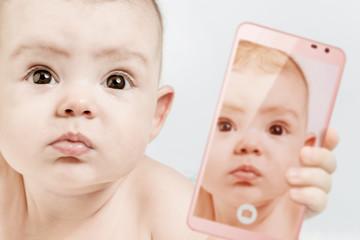 Funny baby girl make selfie on mobile phone