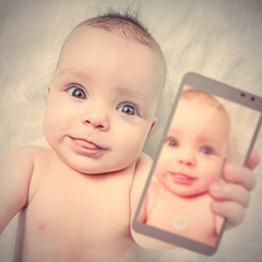 A cute baby shows his selfie photos on a smartphone