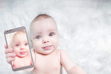 Funny baby girl taking selfie with tongue out