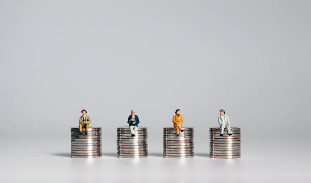 Miniature people sitting on piles of coins. A concept about social costs.