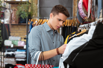 Too expensive. Emotional young man thoughtfully looking at the price and feeling upset while having no money for expensive clothes