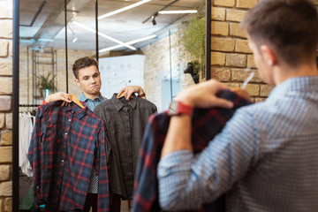 Fashionable shirts. Calm curious young man choosing fashionable clothes in the shop and feeling satisfied while looking at two shirts