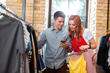 Showing photos. Handsome young person smiling and turning the screen of his smartphone while showing photos to his girlfriend in clothes shop