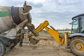 Concrete from a concrete mixer is poured into a bucket of an excavator