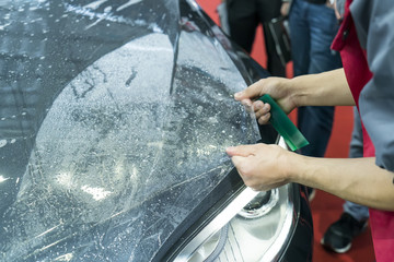 Worker install car paint protection film with spatula