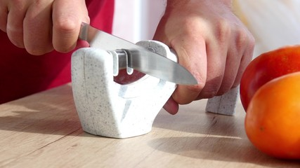 Manual sharpening of a knife in a special sharpener in a kitchen