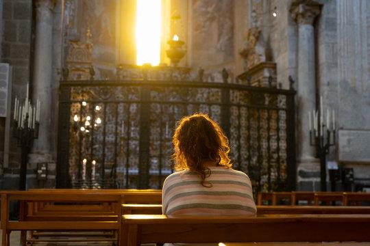 A woman prays sitting at the Catholic altar woman prays sitting at the Catholic altar inside the Church