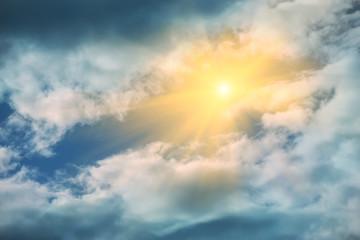 Rays of sun shining in blue sky.
