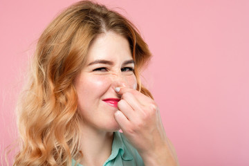 bad rancid smell or terrible odor concept. woman holding her nose and grimacing. emotion expression and reaction concept. young beautiful blond girl portrait on pink background.