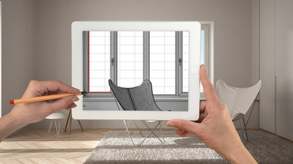 Hands holding and drawing on tablet showing modern living room CAD sketch. Real finished minimalist white and wooden living in the background, architecture interior design presentation