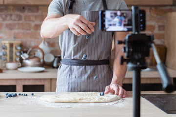 online culinary show. blogging and live video streaming. chef showing the process of blueberry pie cooking.