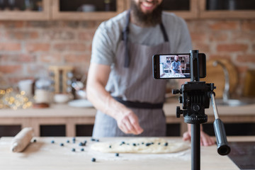 vlogging and freelance job concept. food blogger preparing blueberry pie. cooking and culinary skills concept. bearded man shooting video of himself using camera on tripod.