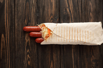 sausages in pita bread on wooden background.photo with copy spac