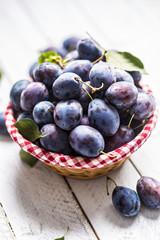 Sweet ripe plums in basket on garden table