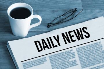 Eine Tasse Kaffee, Brille und Zeitung mit dem Titel Daily News