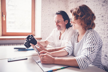 A middle-aged man and a young woman are sitting at a table, a camera and a diary. Training and master classes in photography and processing, education concept, creative professions