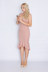 Full length image of smiling blonde woman in beige midi dress