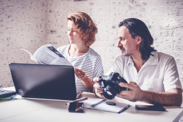 A middle-aged man and a young woman are sitting at a table with a laptop, camera and diary. Training and master classes in photography and processing, education concept, creative professions