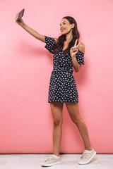 Full length image of Cheerful woman in dress making selfie