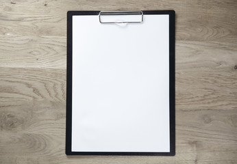 clipboard with blank sheet on wooden background