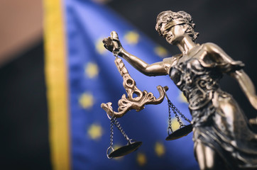 Scales of Justice, Justitia, Lady Justice in front of the European Union flag in the background.