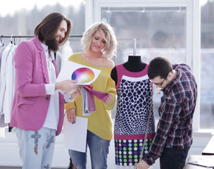 tailor and designers discussing new fabric patterns in creative workshop