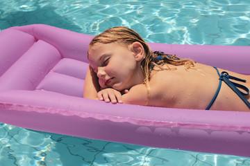 mädchen liegt auf luftmatratze im pool