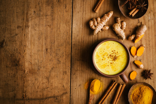 Hot turmeric milk with spices on wooden table