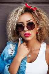 Portrait of beautiful smiling afro american woman in sunglasses in the street.