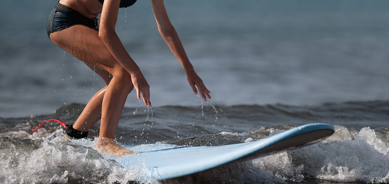 A woman learns to surf on the wave,surfing on the blue waves