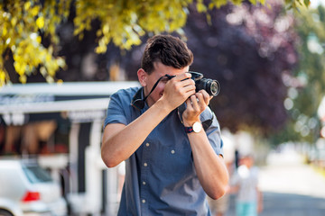 Young professional male photographer using camera at street