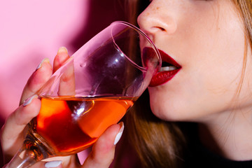Aperol. Girl drinks alcohol. Aperitif. Girl with a bright makeup. Pink background. Style. Image. Blue hat