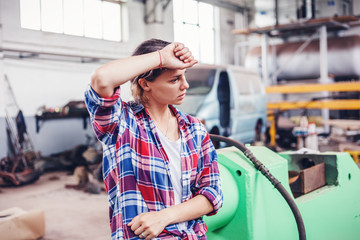 Young beautiful girl working in a workshop for repair of cars and appliances, not female profession, the concept of gender equality, tired from hard work