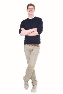 Full body happy young man standing on isolated white background with arms crossed