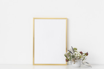 Gold a4 portrait frame mockup with dried field wild flowers in small white poton white wall background. Empty frame, poster mock up for presentation design.