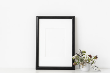 Black a4 portrait frame mockup with small bouquet of flowers in small white pot on white wall background. Empty frame, poster mock up for presentation design.