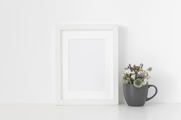 Modern white A5 portrait frame mockup with dried field wild flowers in pot on white wall background. Empty frame, poster mock up for presentation design.