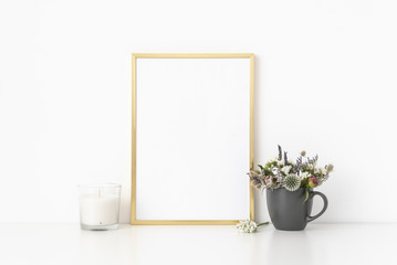 Gold a4 portrait frame mockup with dried field wild flowers in mug and candle on white wall background. Empty frame, poster mock up for presentation design.