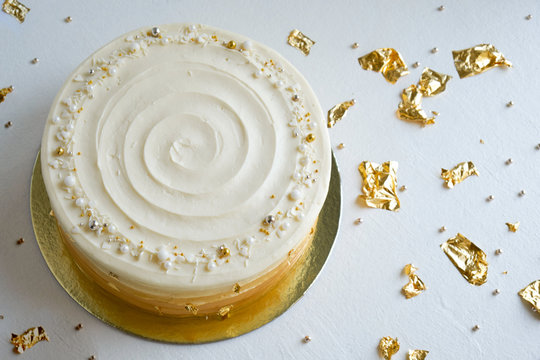 Cake with white cream, decorated with silver and gold confectionery sprinkles and gold leaf on a white background. Picture for a menu or a confectionery catalog. Top view.