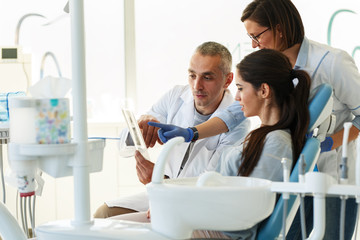 Dentist and his assistant in dental office talking with young female patient and preparing for treatment.Examining x-ray image.