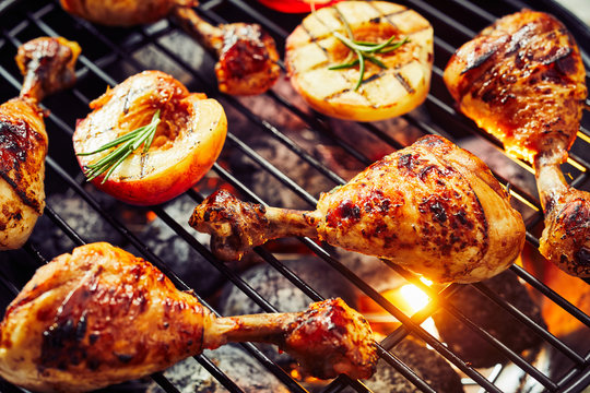 Spicy chicken legs sizzling over a hot barbecue